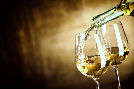 Photo pour Pouring two glasses of white wine from a bottle in a close up view of the wineglasses over an abstract brown blue background with copy space - image libre de droit