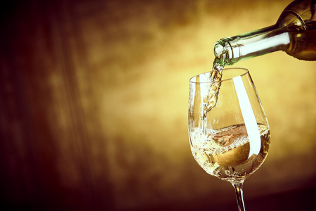 Photo pour Banner of Pouring a glass of white wine from a bottle in a close up view on the elegant wine glass over a blurred brown background with copy space - image libre de droit