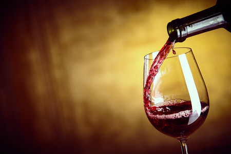Photo for Pouring a single glass of red wine from a bottle in a close up view on the glass over an abstract brown background with copy space - Royalty Free Image