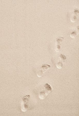 Photo pour Line of footprints in smooth white desert or beach sand crossing diagonally through the frame in a conceptual overhead view with copy space - image libre de droit