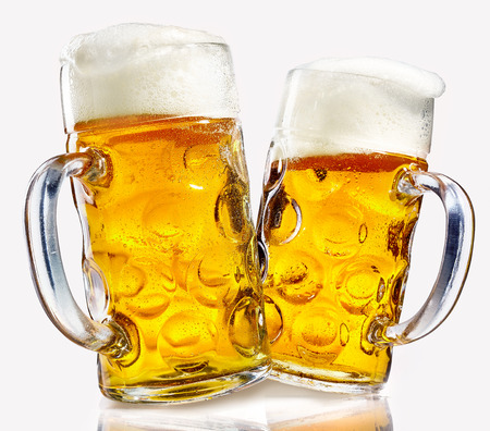 Foto de Two glass beer mugs full of golden lager with thick frothy heads over a reflective white background conceptual of the Oktoberfest - Imagen libre de derechos
