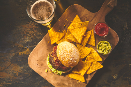 Photo pour Top down view on burger in sesame bun, tortilla chips, salsa and guacamole on cutting board with beer on table - image libre de droit