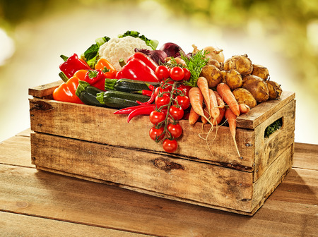 Wooden crate filled with farm fresh vegetables including onions, tomato, peppers, potato, carrots , courgettes and cauliflower, on a wooden table outdoors at market