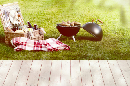 Photo pour Open picnic basket near a folded red checkered tablecloth and a round barbecue grill on the green lawn - image libre de droit