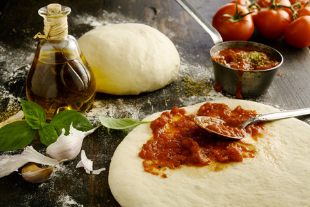 Foto de Ingredients for a delicious homemade Italian pizza with a low angle view of fresh tomato paste being spread on an uncooked dough base with garlic, basil leaves and olive oil alongside - Imagen libre de derechos