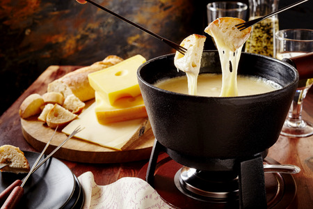 Photo for Gourmet Swiss fondue dinner on a winter evening with assorted cheeses on a board alongside a heated pot of cheese fondue with two forks dipping bread and white wine behind in a tavern or restaurant - Royalty Free Image