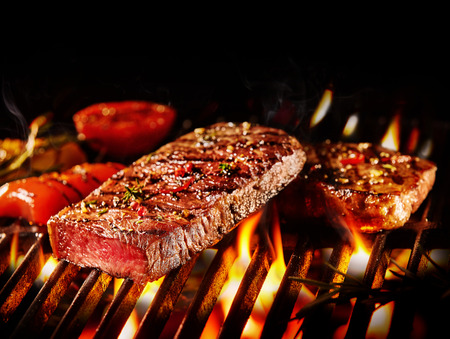 Photo pour Close up on pieces of medium rare beef slice and roasted vegetables on fiery grill - image libre de droit