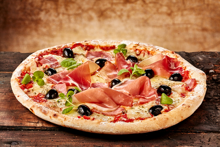 Foto de Close up on single freshly baked bacon, herb, cheese and olive cheese pizza on old table - Imagen libre de derechos