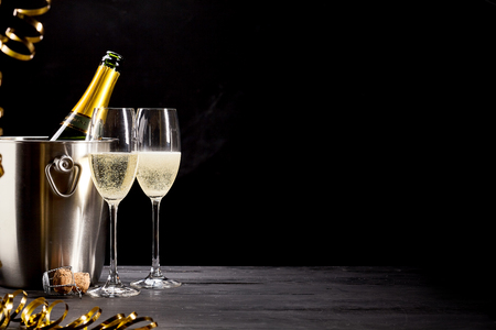 Foto de Sparkling champagne on ice for a romantic celebration with gold party streamers and elegant flutes of bubbly, copy space over a dark background - Imagen libre de derechos