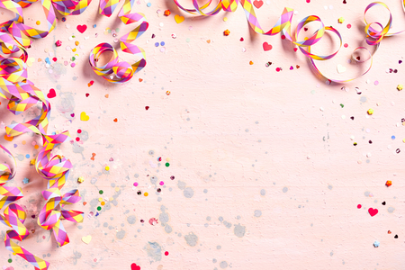 Photo for Delicate pink party background with colorful streamers for celebrating a carnival forming a border around copy space with scattered confetti - Royalty Free Image