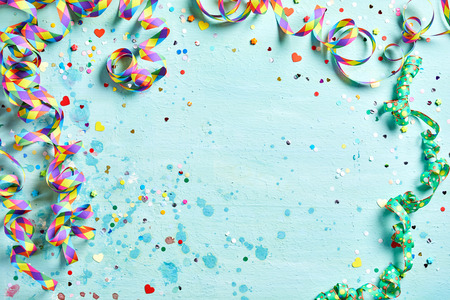 Photo pour Festive party or carnival border of coiled streamers and confetti on a light blue green wood background with copy space - image libre de droit