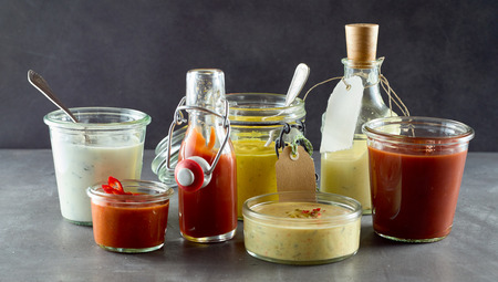 Photo for Selection of assorted sauces and dressings in various containers to serve with takeaway or barbecued food including, relish, chili, ketchup,mayonnaise, mustard, and savory oil - Royalty Free Image