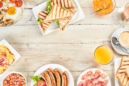 Foto de Various bowls and plates of english breakfast with beans, ham and eggs, orange juice and various sorts of traditional english cuisine in overhead view - Imagen libre de derechos