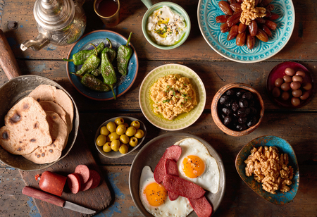 Photo pour Overhead scene of rustic arabian breakfast. Various components of arabic breakfast on an old vintage background plate. - image libre de droit