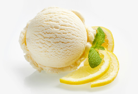 Photo for Tangy fresh lemon citrus sorbet or ice cream with sliced fresh fruit garnished with mint alongside over a white background - Royalty Free Image