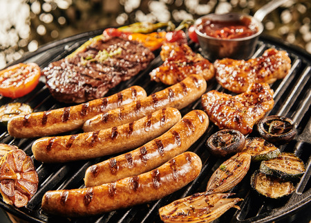 Foto de Delicious summer BBQ grilling over the fire with sausages , chicken wings, steak, mushrooms, tomato, baby marrow, garlic and onion - Imagen libre de derechos
