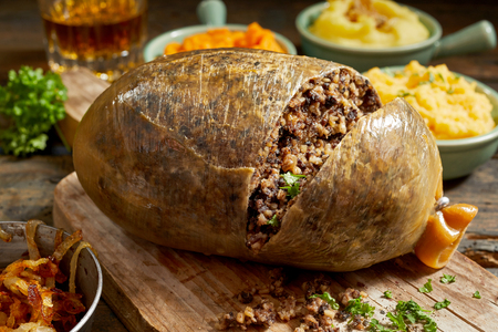 Photo for Sliced open cooked Scottish haggis showing the minced texture of the meat mixture on a wooden board with side dishes of mashed potato, turnip and carrot with fresh herbs - Royalty Free Image