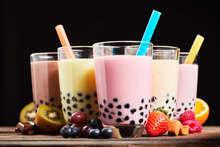 Foto de Glasses of refreshing milky boba or bubble tea with assorted fresh fruit ingredients, chocolate and caramel candy used as flavoring, low angle side view - Imagen libre de derechos