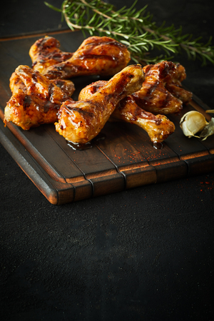 Foto de Portion of delicious marinated spicy chicken legs and wings seasoned with fresh rosemary and served on an old wooden board with copy space below - Imagen libre de derechos