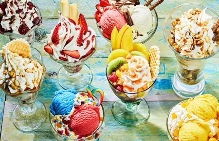 Foto de Assortment of different flavor Italian ice cream sundaes on wooden table - Imagen libre de derechos
