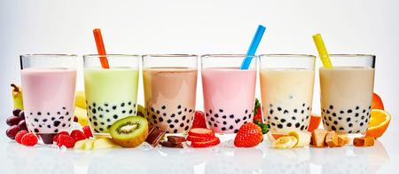 Photo for Asian tea house advertising banner of a choice of different flavored boba teas surrounded with fresh fruit ingredients, and caramel and chocolate candy in a wide panoramic header format on white - Royalty Free Image