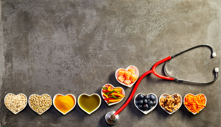 Photo pour Healthy heart food concept with a row of heart-shaped dishes with oats, salmon, turmeric, lentils, peppers, olive oil, acai, walnuts and carrot forming a border with a stethoscope on copy space - image libre de droit
