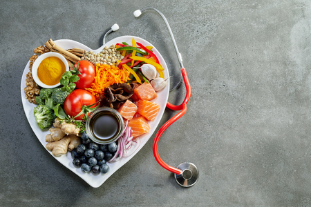 Photo for Fresh food for a healthy heart with acai, lentils, soy sauce, ginger, salmon, carrot, tomato, turmeric, cinnamon, walnuts, garlic, peppers, broccoli, basil, onion with a stethoscope and copy space - Royalty Free Image