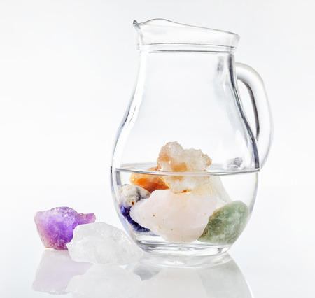 Photo for Transparent glass jug of drinking water with submerged healing stones and colorful minerals, isolated on white background - Royalty Free Image