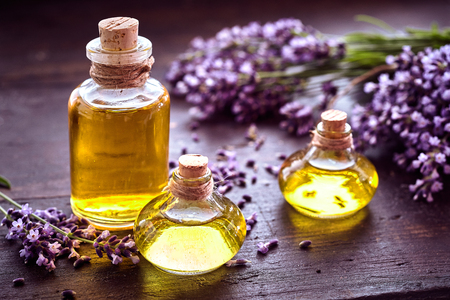Photo pour Bottles of lavender essential oil or extract with sprigs of fresh purple flowers on a rustic wood table in a healthcare or spa concept - image libre de droit