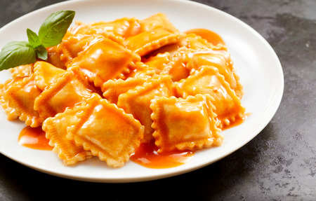 Foto de Plate of tasty traditional Italian ravioli pasta served in a piquant spicy sauce garnished with basil in a close up view - Imagen libre de derechos