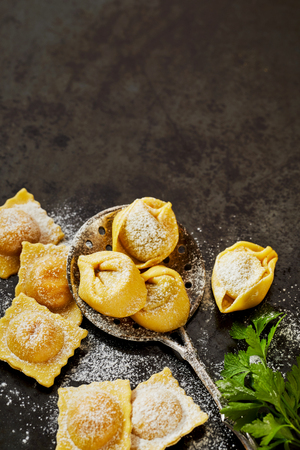 Photo pour Fresh uncooked handmade Italian tortellini and ravioli pasta with a vintage spoon and basil on a dark textured surface with copy space viewed from above - image libre de droit