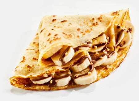 Photo for Fresh banana crepes drizzled with chocolate sauce and chopped nuts and folded into quarters on a white background - Royalty Free Image