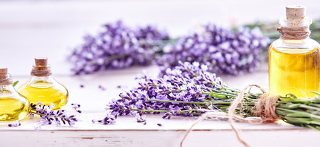 Photo pour Panorama banner of fresh lavender flowers tied in bunches and essential oils in decorative flacons on a white wood background with copy space and shallow dof for advertising - image libre de droit