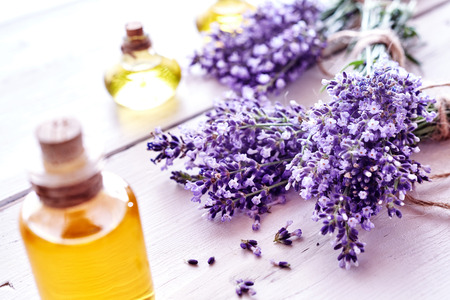 Photo pour Fresh aromatic purple lavender flowers with bottles of essential oil or extracts in a spa, alternate medicine, perfumery and wellness concept on white wood - image libre de droit