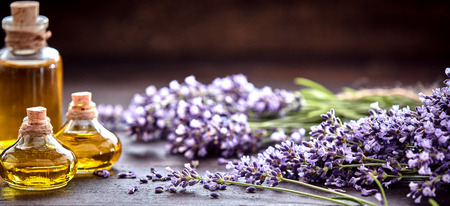 Photo pour Panorama banner of decorative bottles of lavender essential oil with bunches of freshly picked aromatic purple flowers on a rustic wood table with copy space above - image libre de droit