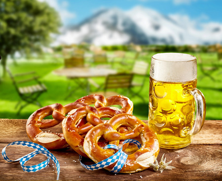 Foto de Pretzels and frothy pint of beer in a glass tankard to celebrate Oktoberfest served on a rustic wooden table outdoors in a tavern with a view of the snowy alps - Imagen libre de derechos