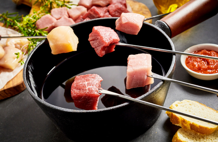Foto de Assorted meat ready to be dipped in a fondue pot with beef, veal, pork and chicken breast displayed on forks - Imagen libre de derechos