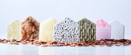 Photo pour Seven house shapes made from various building materials in a triangle formation surrounded by coins. - image libre de droit