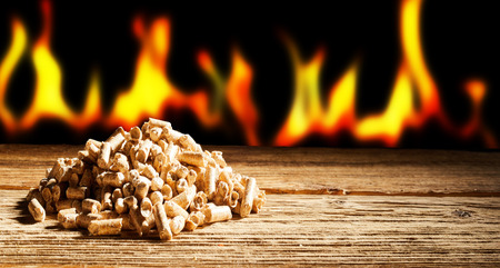 Photo for Renewable or sustainable energy concept with a row of burning flames behind a heap of natural wood pellets in a panorama view with copy space - Royalty Free Image
