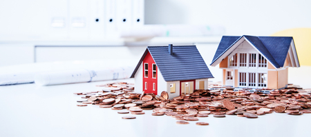 Photo pour Two miniature houses among pile of coins - image libre de droit