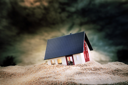 Foto de Small model of house built on pile of sand - Imagen libre de derechos