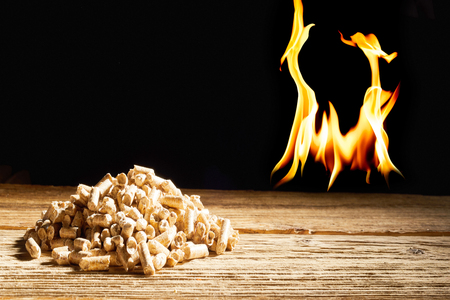 Photo for Flames burning in the darkness behind a heap of wood pellets on a rustic table in a concept of natural renewable fuel and energy with copy space - Royalty Free Image