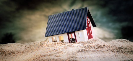 Foto de Miniature of house standing in pile of sand - Imagen libre de derechos