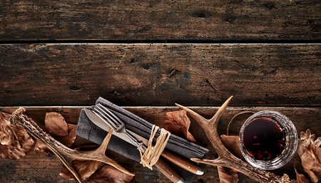 Photo pour Stag antlers, brown autumn leaves, knife, fork and a glass of whiskey on a rustic wooden background. - image libre de droit