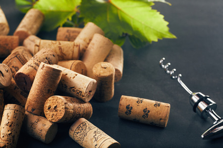 Photo pour Bunch of wine corks with corkscrew and grape leaf in background - image libre de droit