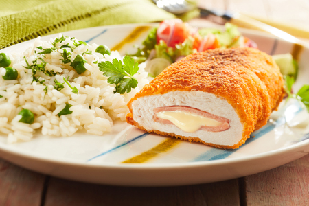 Foto de Fired cordon bleu chicken served with rice and parsley on plate - Imagen libre de derechos