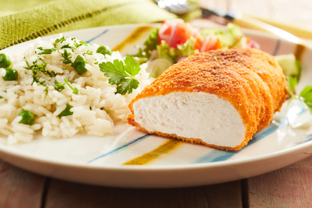 Foto de Fried chicken breast served with rice and salad on plate - Imagen libre de derechos