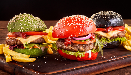 Photo pour Three colorful Asian beef and cheese burgers with French Fries on red, green and black sesame buns served on a wooden board - image libre de droit