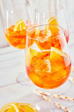 Foto de A close up of refreshing aperol orange spritz cocktails and glasses with a plain white timber background. - Imagen libre de derechos