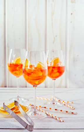 Photo for Refreshing aperol spritz cocktails with straws and sliced orange on a white timber table in vertical portrait orientation. - Royalty Free Image